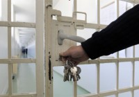Man with keys opening prison door