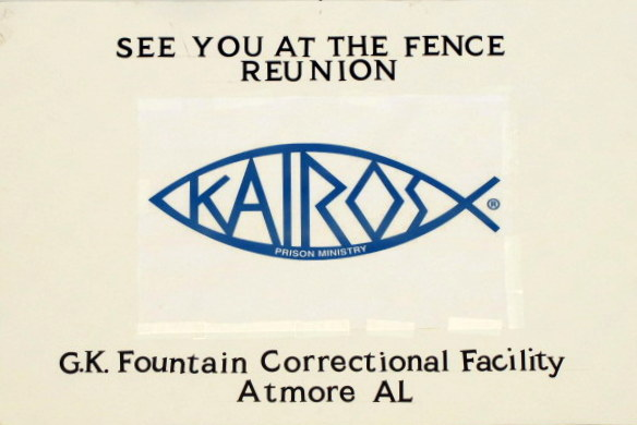 "A sign used by the volunteers that has a Kairos blue fish logo and the text ""See You at the Fence Reunion"" at the top and ""G.K. Fountain Correctional Facility Atmore, AL"" at the bottom"