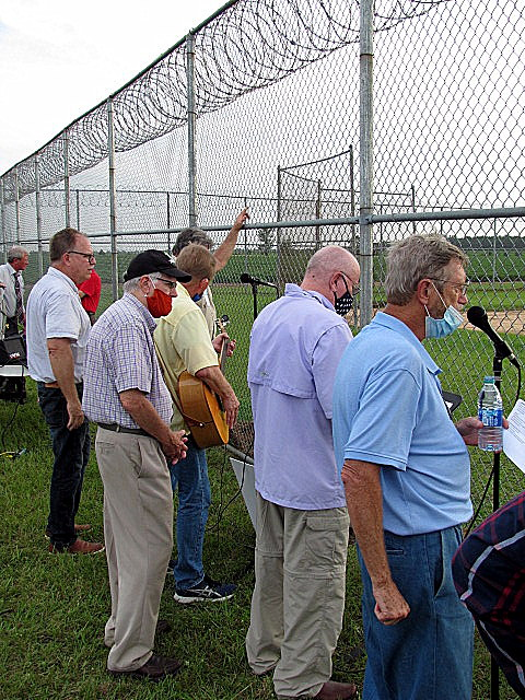 A photo of a handful of the volunteers at the prison fence, all with masks and some are in front of microphones and a couple holding but not playing guitars.