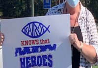 "A women holding a sign that says ""Kairos Knows that Heroes Work Here"""