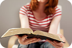 Young woman reading Holy Bible