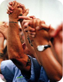 Kairos Inside Graduate prisoners raising clasped hands in celebration