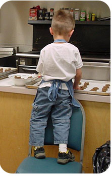 A little boy making cookies for Kairos